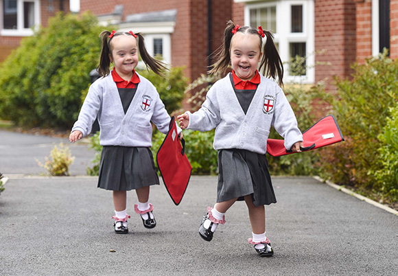 """PIC BY Dan Rowlands/Mercury Press (PICTURED: 4 YEAR OLD DOWN'S SYNDROME TWINS ABIGAIL AND ISOBEL RUN AFTER EACH OTHER) Identical twins born with Down's syndrome at odds of two million to one have celebrated a milestone their parents thought they might never see. Happily, it looks like teachers telling them apart will be the biggest worry for Abigail and Isobel Parry on their first day of school. The adorable four-year-olds were diagnosed with Down's syndrome three weeks after their premature birth in June 2011. Parents Matt and Jodi Parry admit they first thought this was """"a life sentence"""" – but now devote their lives to busting myths and misconceptions around the genetic condition. SEE MERCURY COPY"""